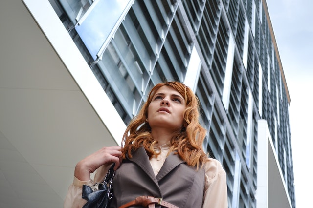 woman-looking-at-modern-office-building-314635